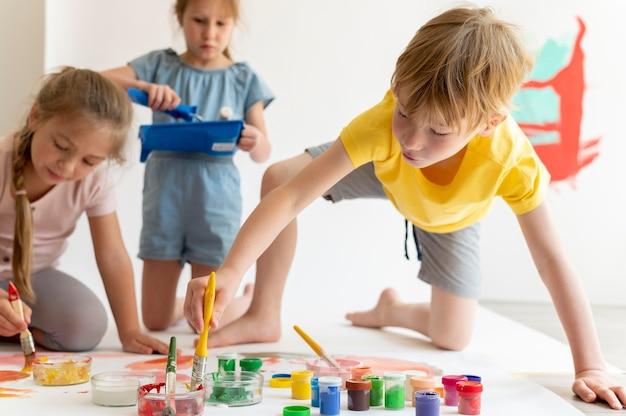 Średnie ujęcia dzieci z farbą