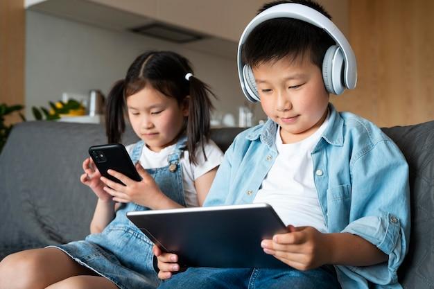 Średnie ujęcia dzieci z urządzeniami