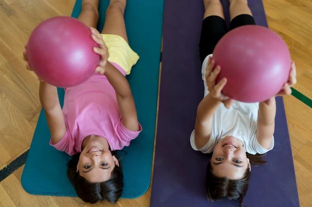 Średnie ujęcia dziewczyny na matach do jogi z piłkami