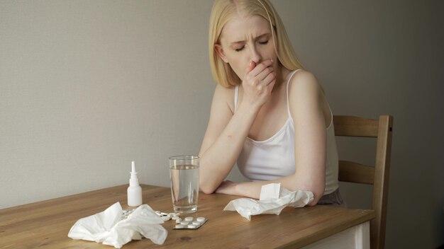 Średnie ujęcie blond kobieta z bólem gardła, siedząc przy stole w kuchni i kaszle.
