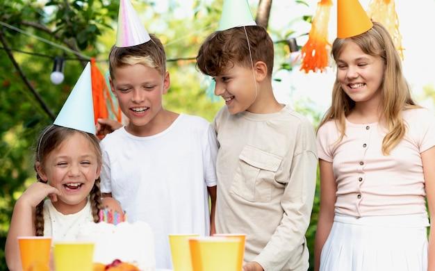 Średnie ujęcie buźki dla dzieci z imprezowymi czapeczkami