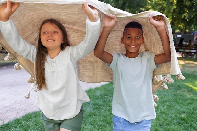 Średnie ujęcie dzieci bawiące się kocem