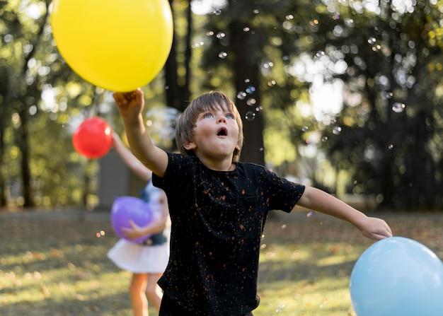 Średnie ujęcie dzieci bawiące się na zewnątrz