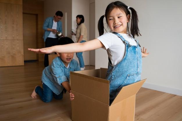 Średnie ujęcie dzieci bawiące się pudełkiem