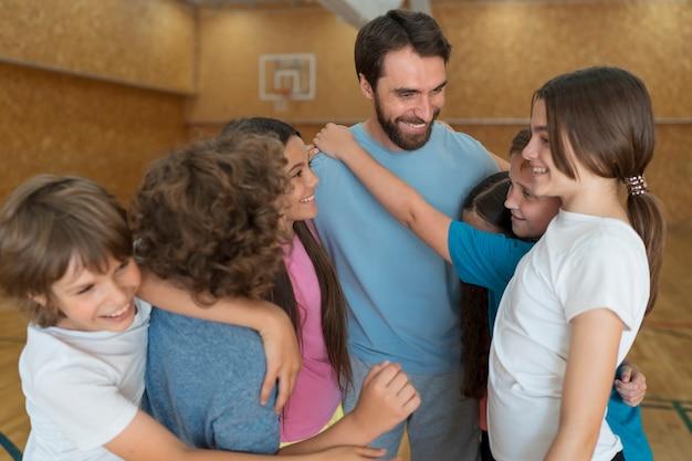 Średnie ujęcie dzieci i nauczyciel wychowania fizycznego