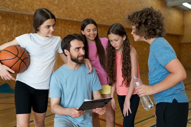 Średnie ujęcie dzieci i nauczyciela dyskutujące