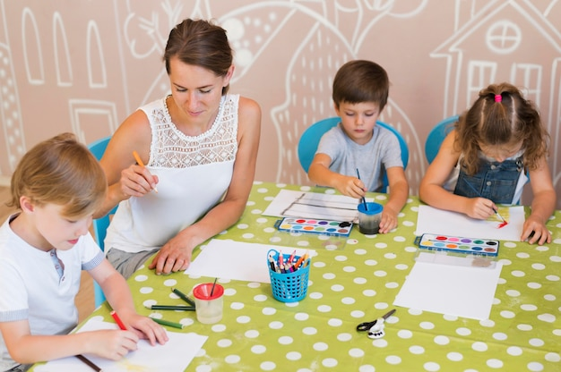 Średnie ujęcie dzieci malujących przy stole