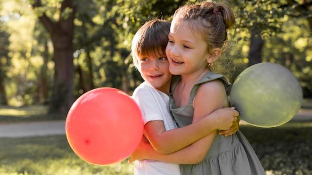 Średnie ujęcie dzieci przytulających się na zewnątrz
