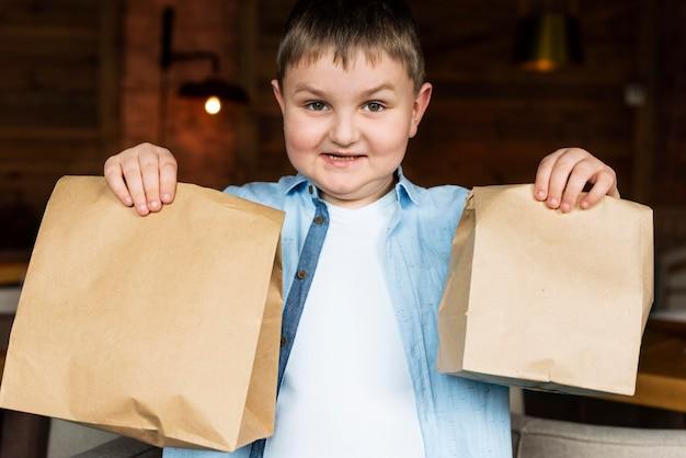Średnie ujęcie dzieci trzymających papierowe torby