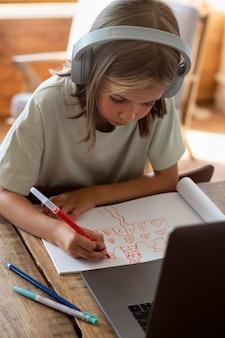Średnie ujęcie dzieciaka rysującego w domu