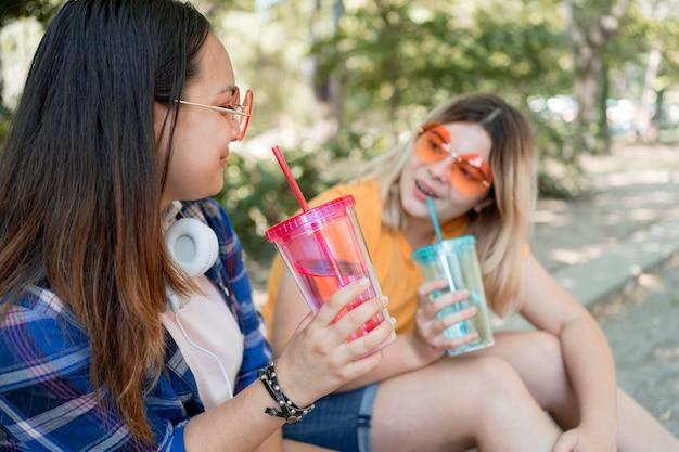 Średnie ujęcie dziewcząt trzymających napoje