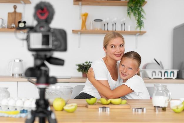 Średnie ujęcie dziewczyny i kobiety nagrywającej kamerą