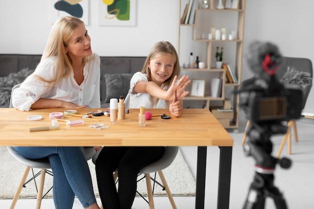 Średnie ujęcie dziewczyny i kobiety nagrywającej wideo