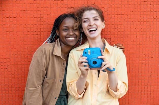 Średnie ujęcie kobiety pozujące z aparatem