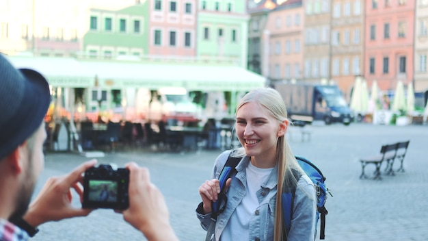 Średnie ujęcie mężczyzny robiącego zdjęcia turystki na rynku miasta. blondynka robi miny i uśmiechając się.