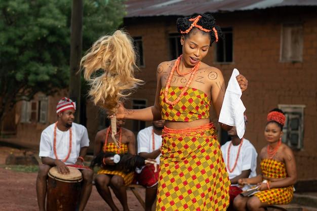 Średnie ujęcie nigeryjskich tancerzy na świeżym powietrzu