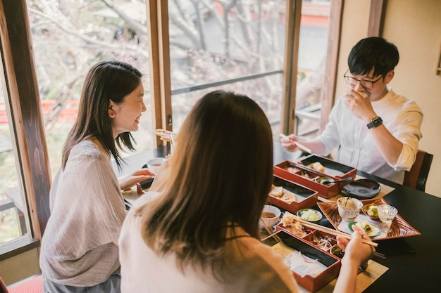 Średnie ujęcie osób siedzących razem przy stole