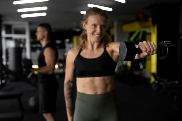 Średnie ujęcie osób trenujących razem na siłowni