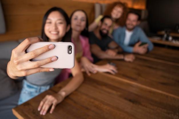 Średnie ujęcie, rozmazani przyjaciele robiący selfie
