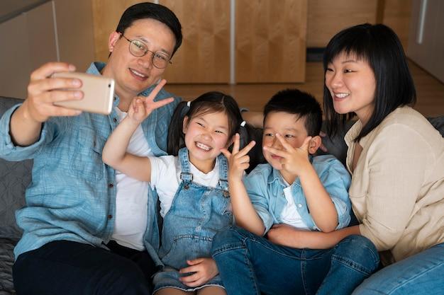 Średnie ujęcie szczęśliwa rodzina biorąca selfie