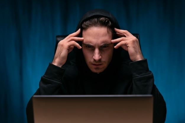 Średnie ujęcie zaniepokojonego mężczyzny z laptopem