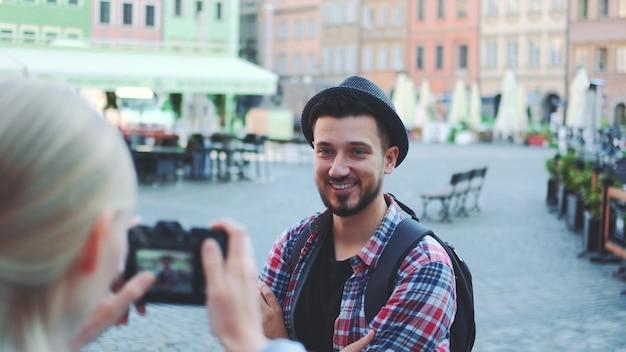Średnie zbliżenie pary turystów wykonujących zdjęcia aparatem fotograficznym na historycznym rynku. mężczyzna pozowanie i kobieta robienia zdjęć.