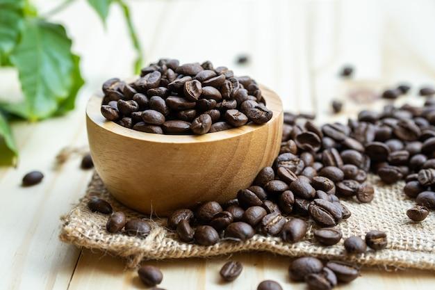 Średnie ziarno kawy prażone w drewnianej misce z liśćmi świeżego poranka.