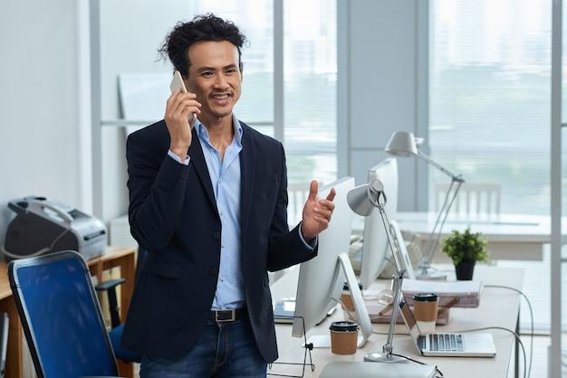 Średniej długości azjatycki przedsiębiorca rozmawia przez telefon w swoim lekkim biurze