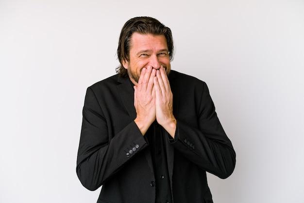 Średnim wieku holenderski mężczyzna na białym tle śmiejąc się o czymś, obejmując usta rękami.