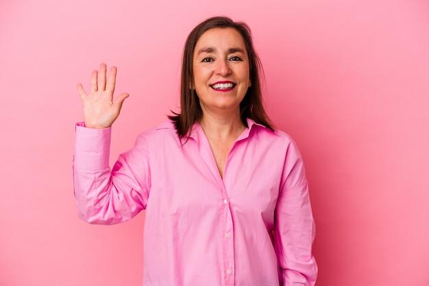 Średnim wieku kaukaski kobieta na białym tle na różowym tle uśmiechnięty wesoły pokazując numer pięć palcami.