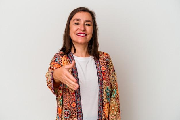 Średnim wieku kaukaski kobieta na białym tle rozciągając rękę w aparacie w geście pozdrowienia.