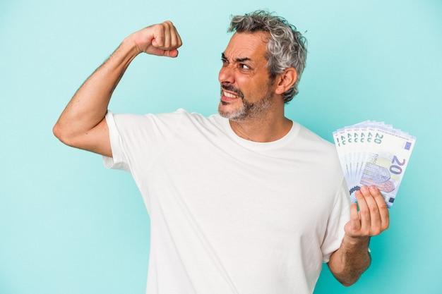 Średnim wieku kaukaski mężczyzna gospodarstwa rachunki na białym tle na niebieskim tle podnosząc pięść po zwycięstwie, koncepcja zwycięzca.