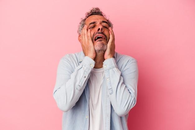 Średnim wieku kaukaski mężczyzna na białym tle na różowym tle płacz, niezadowolony z czegoś, koncepcja agonii i zamieszania.