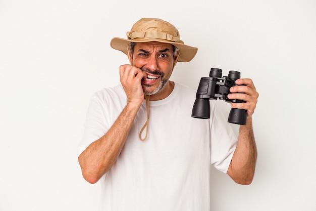 Średnim wieku kaukaski mężczyzna trzyma lornetkę na białym tle gryząc paznokcie, nerwowy i bardzo niespokojny.