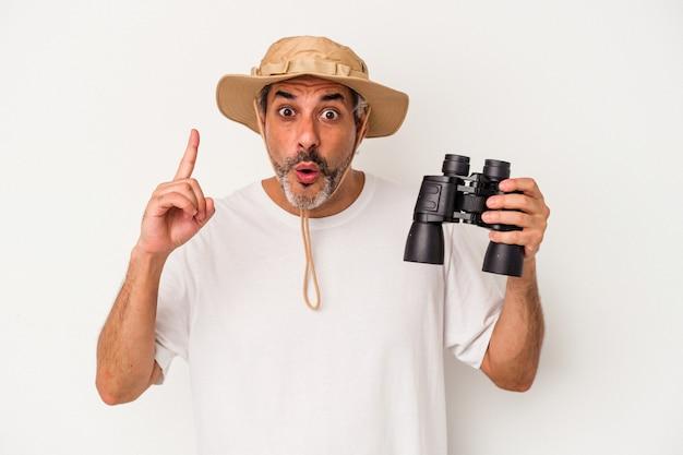 Średnim wieku kaukaski mężczyzna trzyma lornetkę na białym tle o pomysł, koncepcja inspiracji.