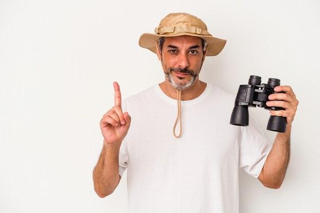 Średnim wieku kaukaski mężczyzna trzyma lornetkę na białym tle pokazując numer jeden palcem.