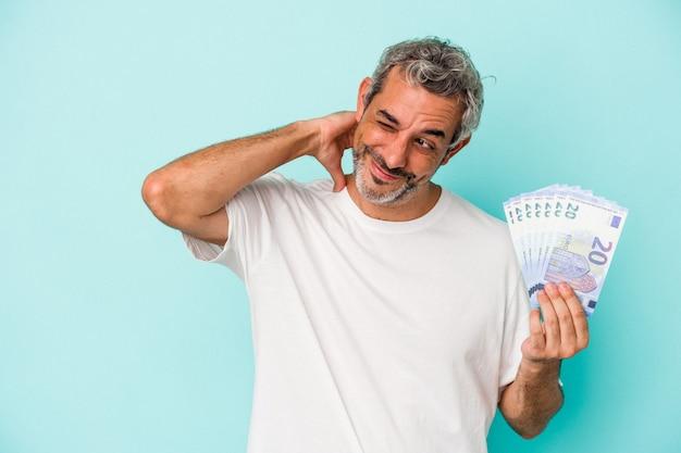 Średnim wieku kaukaski mężczyzna trzyma rachunki na białym tle na niebieskim tle dotykając tyłu głowy, myśląc i dokonując wyboru.