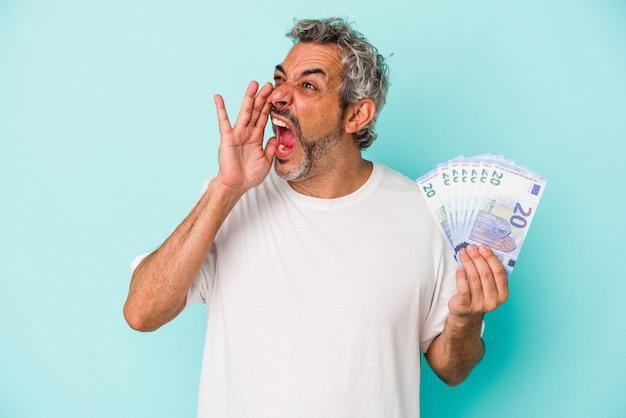 Średnim wieku kaukaski mężczyzna trzyma rachunki na białym tle na niebieskim tle krzycząc i trzymając dłoń w pobliżu otwartych ust.
