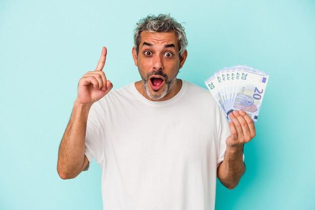 Średnim wieku kaukaski mężczyzna trzyma rachunki na białym tle na niebieskim tle mając pomysł, koncepcję inspiracji.