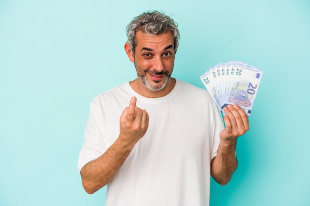 Średnim wieku kaukaski mężczyzna trzyma rachunki na białym tle na niebieskim tle, wskazując palcem na ciebie, jakby zapraszając się bliżej.