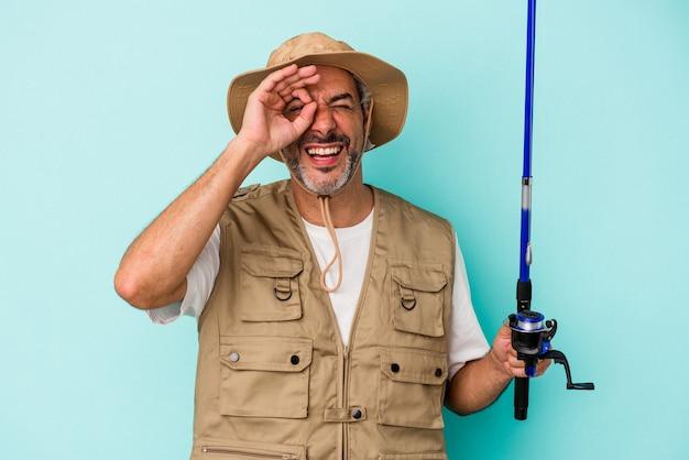 Średnim wieku kaukaski rybak trzymając pręt na białym tle na niebieskim tle podekscytowany, zachowując ok gest na oko.