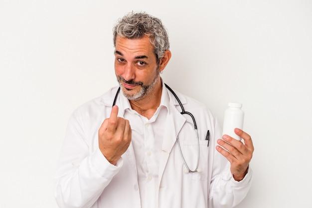 Średnim wieku lekarz kaukaski mężczyzna na białym tle wskazując palcem na ciebie, jakby zapraszając się bliżej.