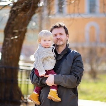 Średnim wieku ojciec z synem malucha chodzić i bawić się na zewnątrz w ciepły dzień wiosny
