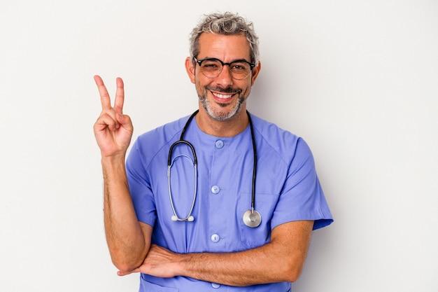 Średnim wieku pielęgniarka kaukaski mężczyzna na białym tle na białym tle pokazując numer dwa palcami.