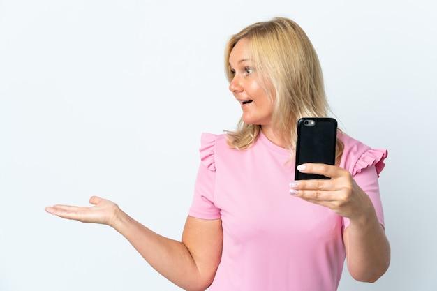 Średnim wieku przy użyciu telefonu komórkowego na białym tle z zaskoczeniem wyraz twarzy