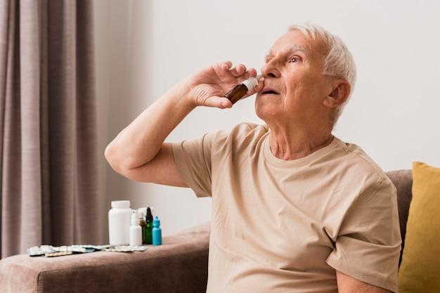 Średnio postrzelony mężczyzna używający sprayu do nosa