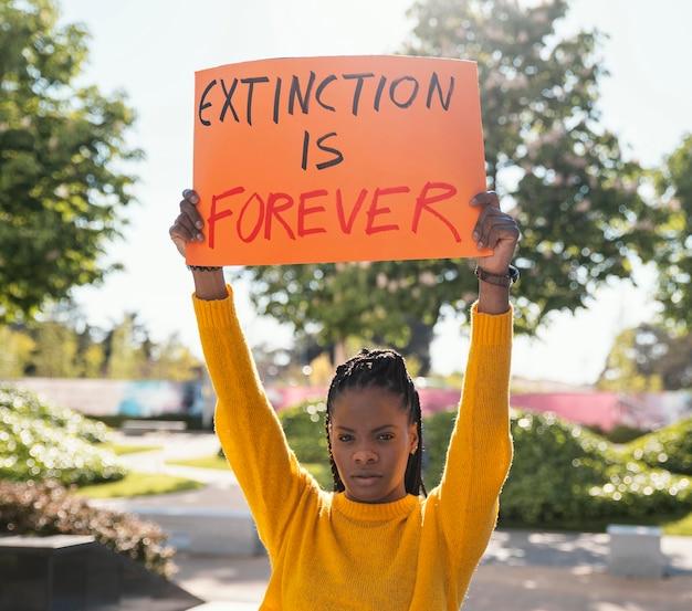 Średnio strzał aktywistka trzymająca tabliczkę