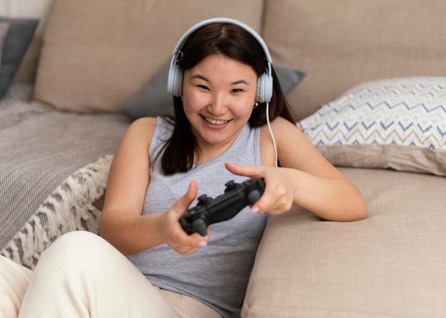 Średnio strzał buźka kobieta grająca w grę wideo
