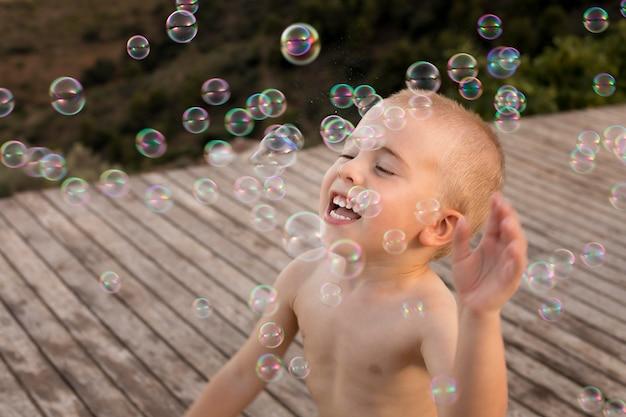 Średnio strzał chłopiec z mydlanymi balonami