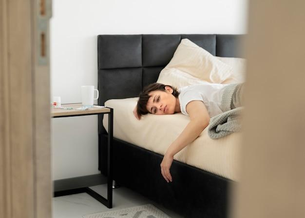 Średnio strzał chora kobieta w łóżku